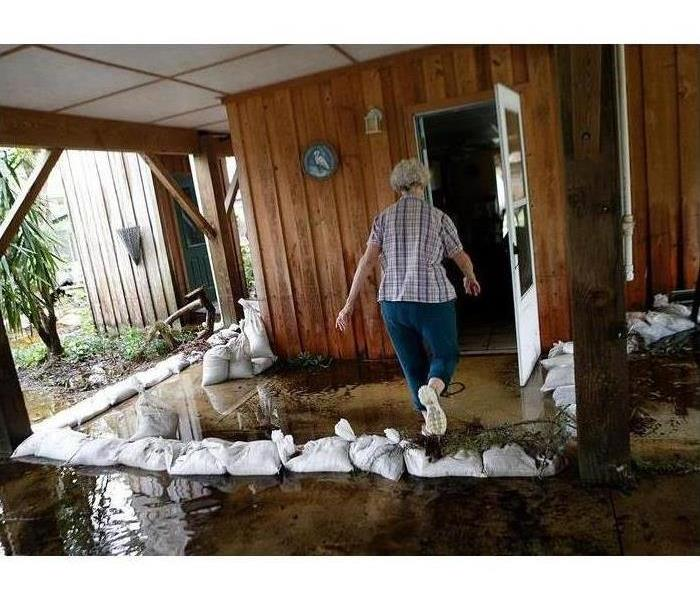a picture of a lady walking through a flooded patio